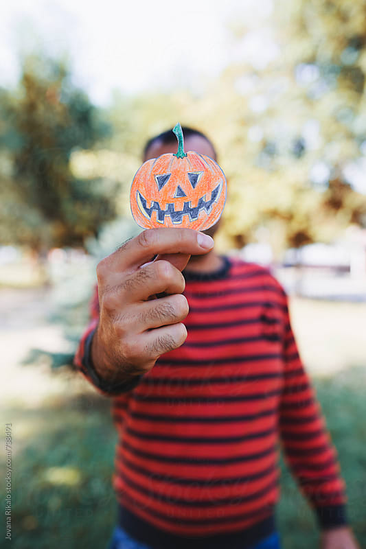 Portrait of a man holding halloween pumpkin made out of a paper in front of his face by Jovana Rikalo for Stocksy United