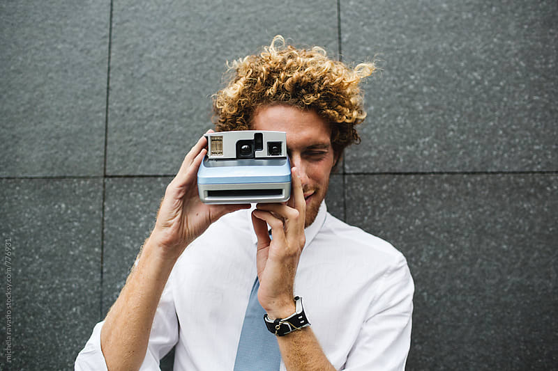 Man taking pictures with an instant camera by michela ravasio for Stocksy United
