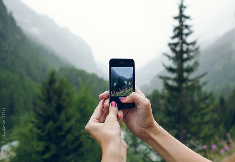 Woman taking a photo up in the mountains with her phone by Denni Van Huis for Stocksy United