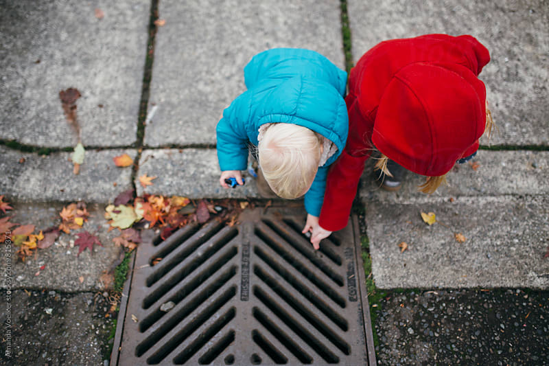 Birds Eye View of Two Young Children on the Sidewalk in Bright coats by Amanda Voelker for Stocksy United