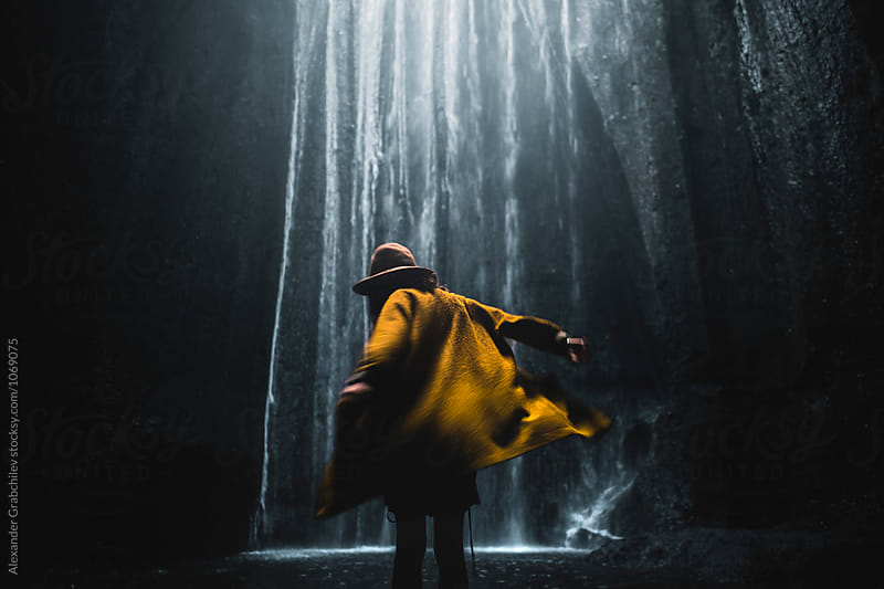 woman  in yellow coat whirling near waterfall by Alexander Grabchilev for Stocksy United