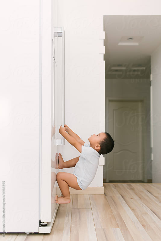 Toddler boy hanging on to door of the fridge by MaaHoo Studio for Stocksy United