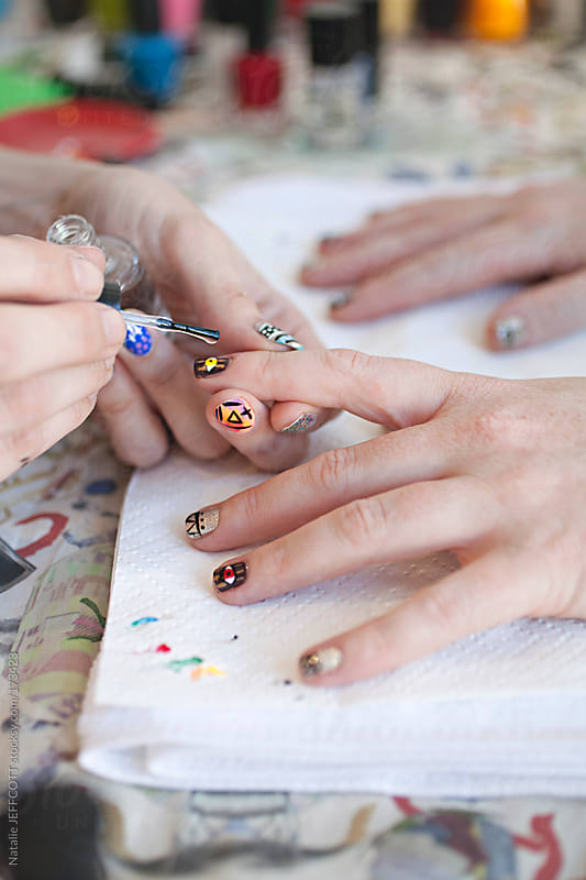 close up of a lady's hands on table top getting her nails done / manicure / nail art by Natalie JEFFCOTT for Stocksy United