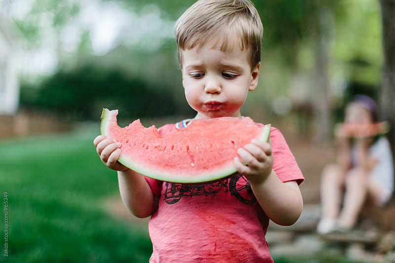 Cute young boy eating watermelon outside by Jakob for Stocksy United