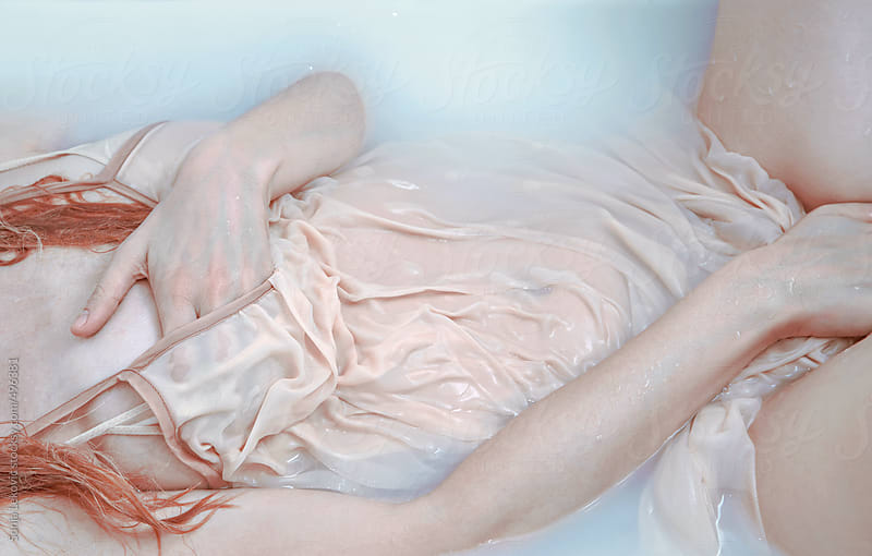 woman in blue water with hands over her intimate parts by Sonja Lekovic for Stocksy United