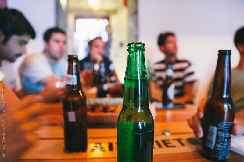 Bottle of beer on a table of a bar with friends watching sports match on TV by Alejandro Moreno de Carlos for Stocksy United