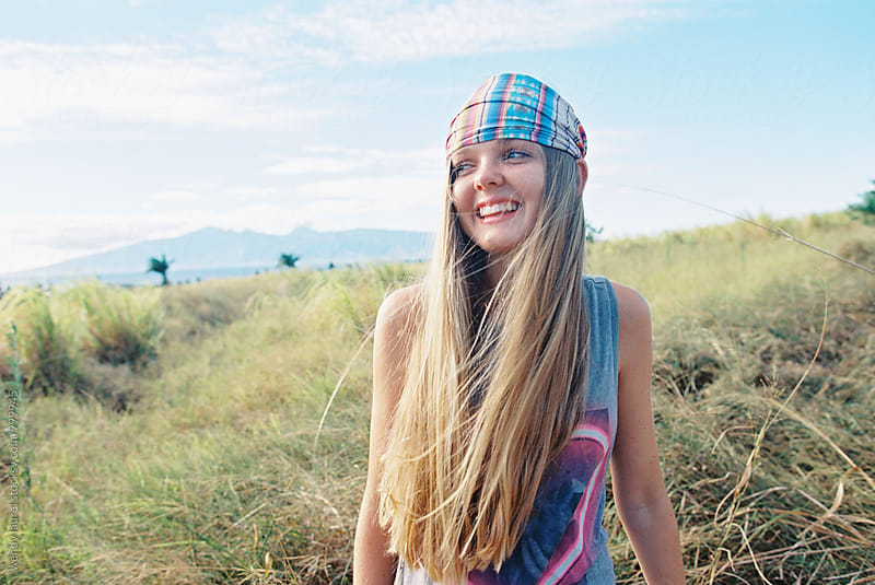 rainbow headband on girl smiling with joy in field by wendy laurel for Stocksy United