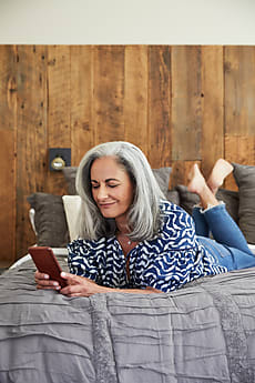 Mature Woman With Grey Hair Texting On Her Mobile Phone By Trinette Reed For Stocksy United
