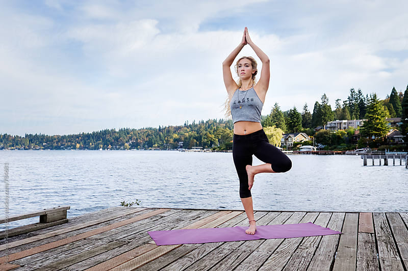 Beautiful young woman practicing yoga near a lake by Suprijono Suharjoto for Stocksy United