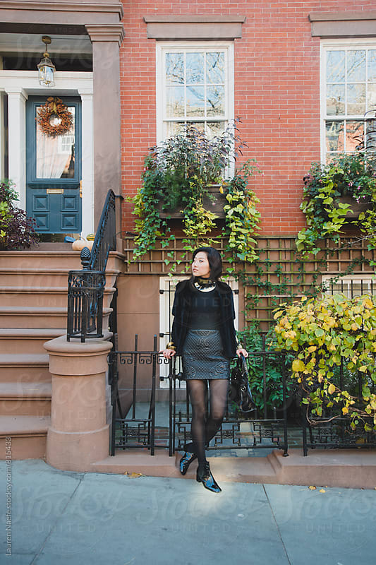 Stylish woman standing outside of townhouse by Lauren Naefe for Stocksy United
