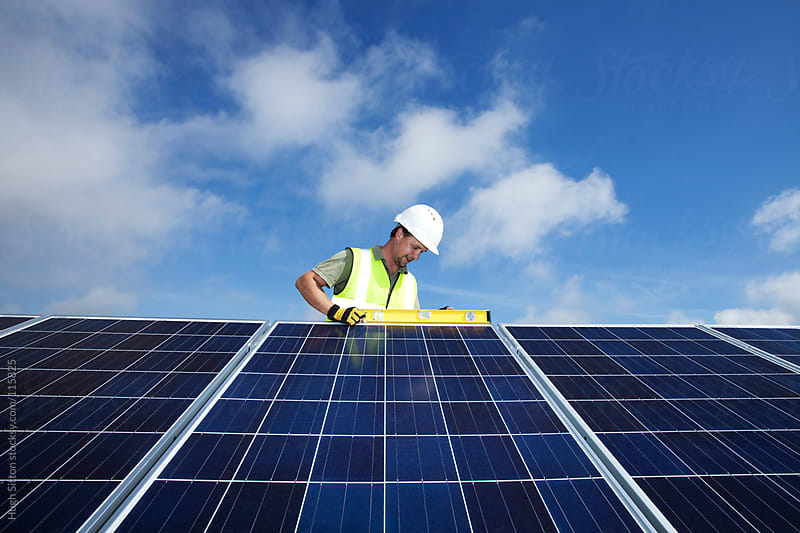 Technician working on solar panels. by Hugh Sitton for Stocksy United