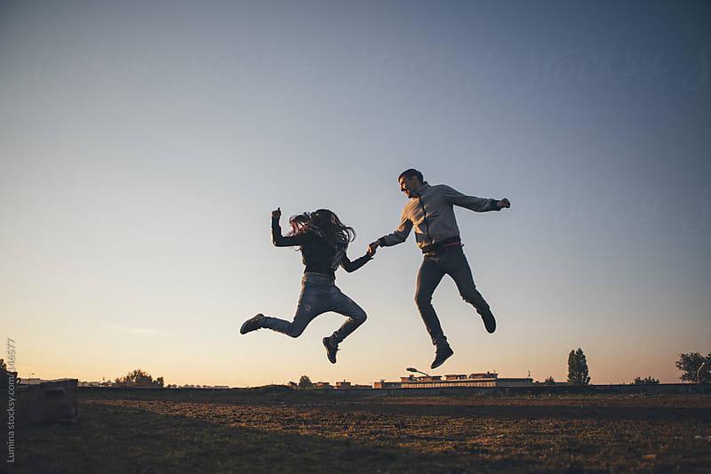 Happy Couple Jumping by Lumina for Stocksy United