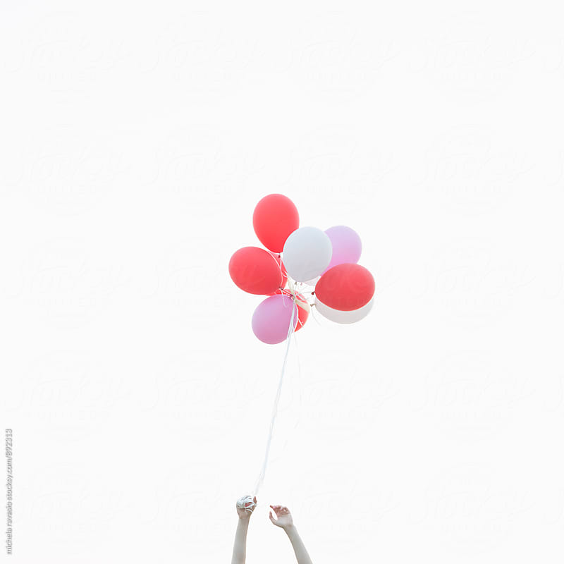 Female hand holding bunch of balloons by michela ravasio for Stocksy United
