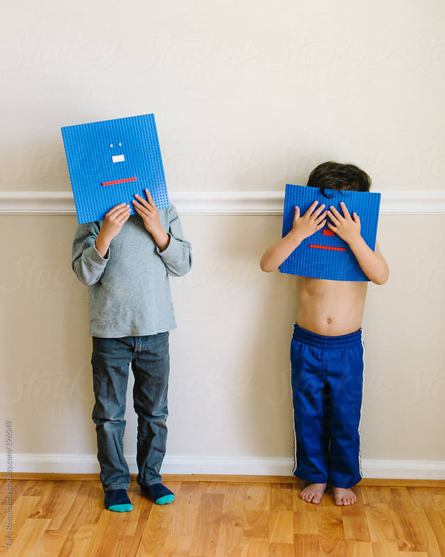 two little boys hide their faces behind blue building block toy emoticon faces by Tara Romasanta for Stocksy United