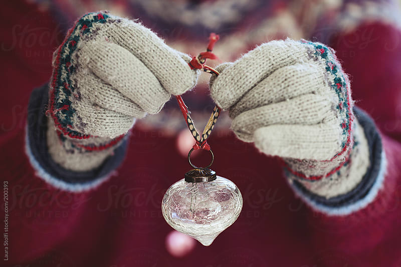 Hands wearing woolen gloves and putting a vintage glass ball on Christmas tree by Laura Stolfi for Stocksy United