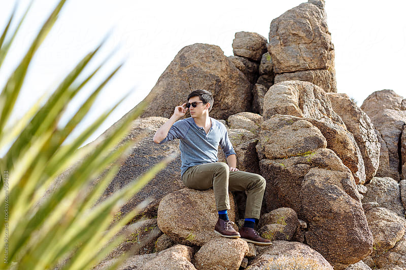 Portrait of a man sitting on a rock in the desert by Melanie Riccardi for Stocksy United