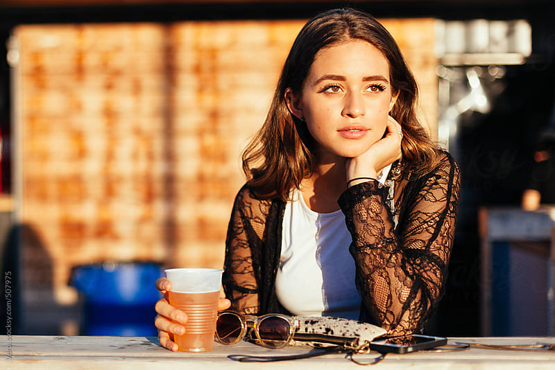 Brunette having a beer at sunset by Good Vibrations Images for Stocksy United