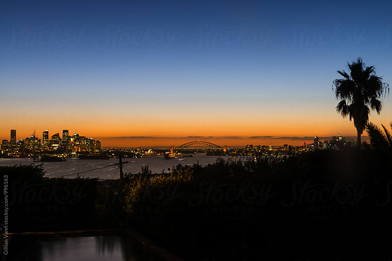 sunset of sydney skyline with the city, Harbour Bridge and Opera House, as seen from Vaucluse by Gillian Vann for Stocksy United