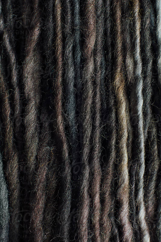Close up detail of grey and earth tone wool yarn by Kristin Duvall for Stocksy United