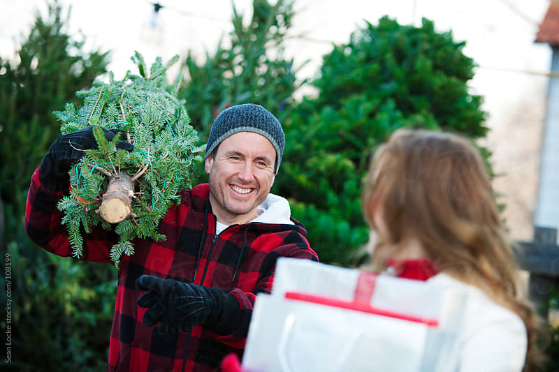 Tree Lot: Employee Helps Woman with Christmas Tree by Sean Locke for Stocksy United