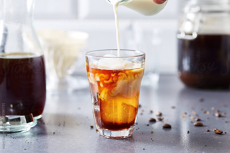 milk pour in glass with black cold coffee by Martí Sans for Stocksy United