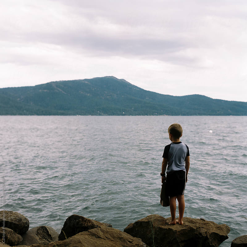 Boy stands alone on a rock facing a lake on a dark and stormy day
