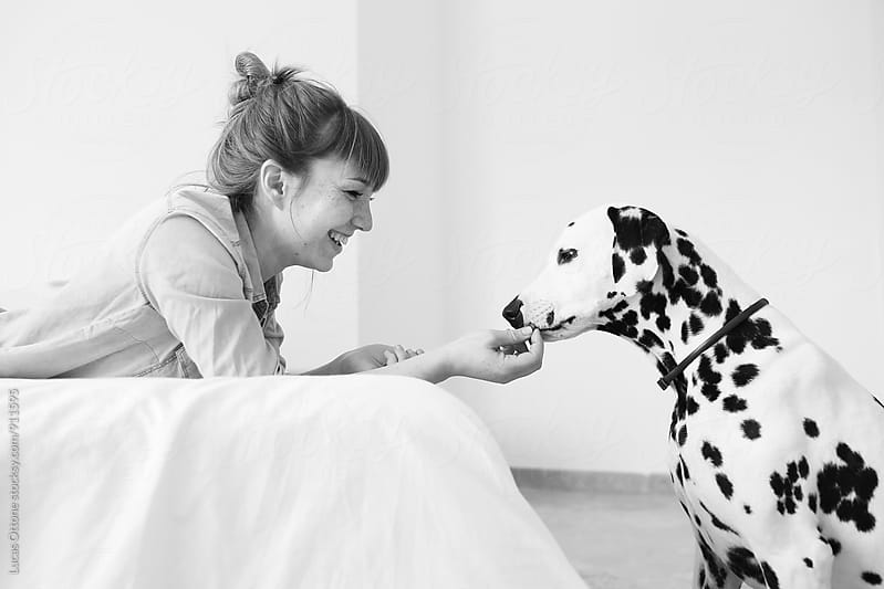 Black and white: Blonde girl playing with a dalmatian dog by Lucas Ottone for Stocksy United