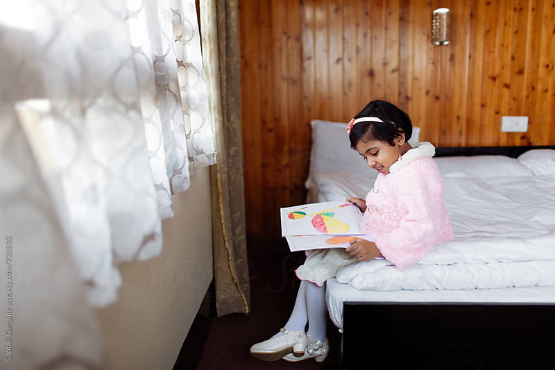 Little girl looking at a drawing book and smiling by Saptak Ganguly for Stocksy United