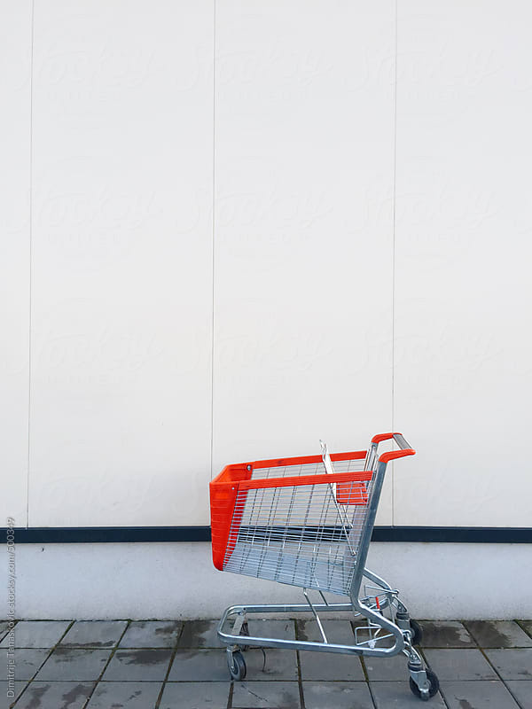 Shopping cart in front of the shopping mall by Dimitrije Tanaskovic for Stocksy United