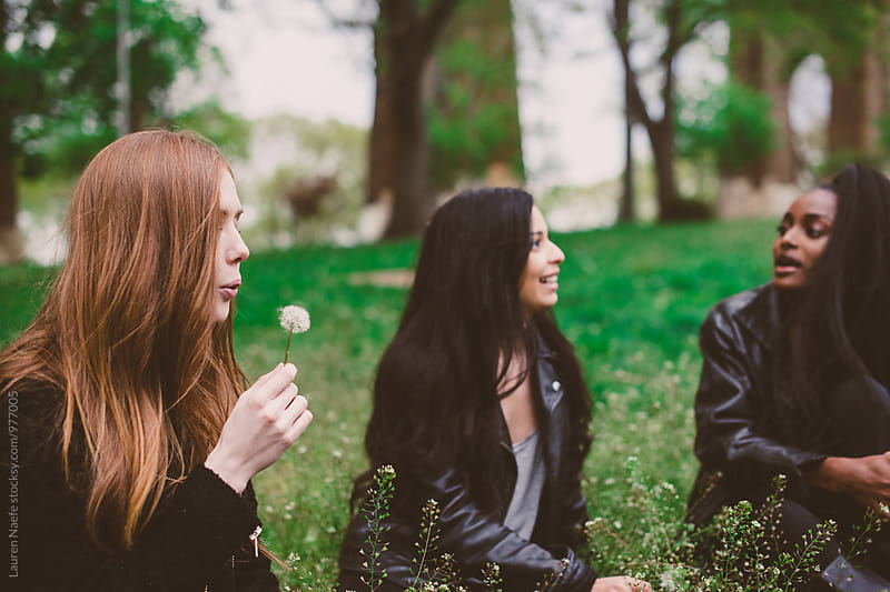 Young woman blowing dandelion and hanging out with friends in field by Lauren Naefe for Stocksy United