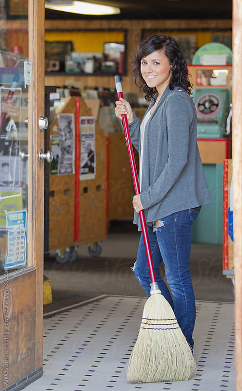 Portrait of young woman with broom at record shop by Andersen Ross Photography for Stocksy United