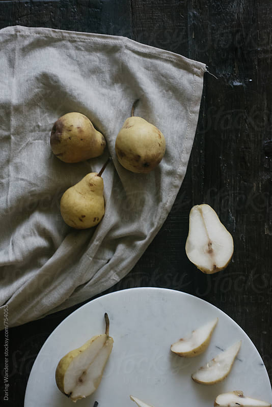 Sliced pears on a marble cutting board on a dark wood table by Daring Wanderer for Stocksy United