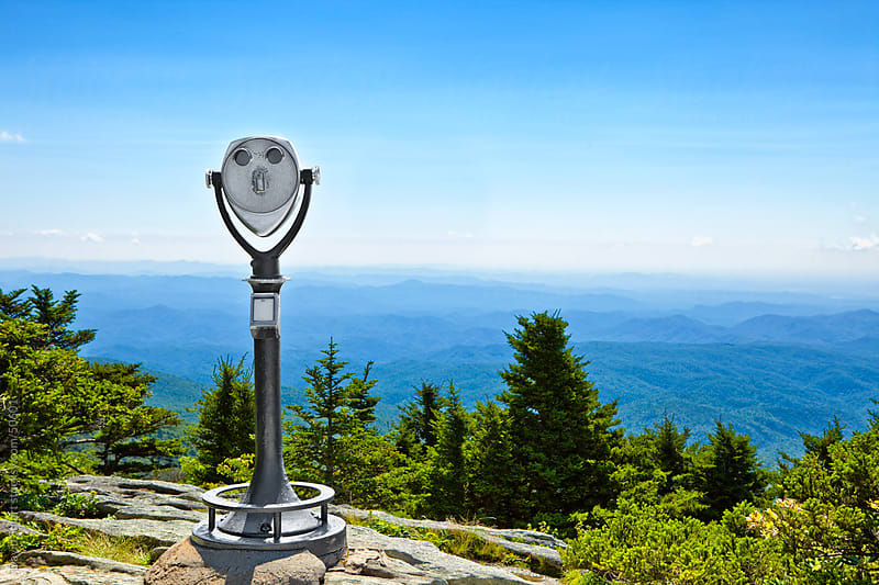 Coin operated telescope stands before a hazy blue ridge mountain by David Smart for Stocksy United