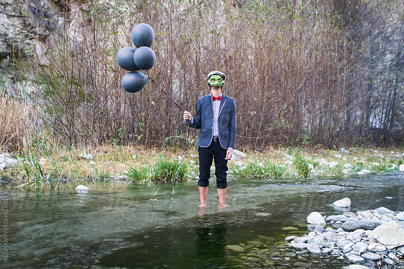 Man Wearing Creepy Frog Mask and Black Balloons in Stream by Meg Pinsonneault for Stocksy United