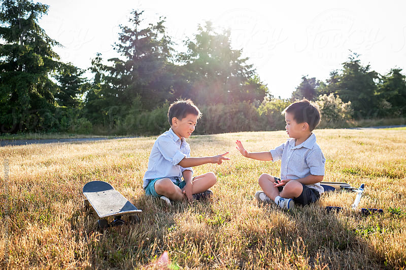 Happy Asian kids playing rock paper scissors outdoor in a park by Suprijono Suharjoto for Stocksy United