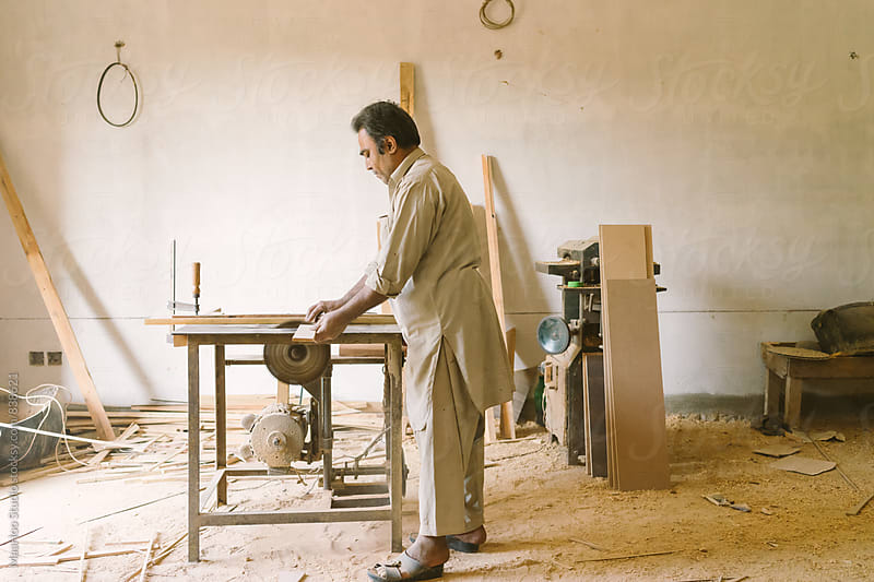 Carpenter working on machine by Maa Hoo for Stocksy United