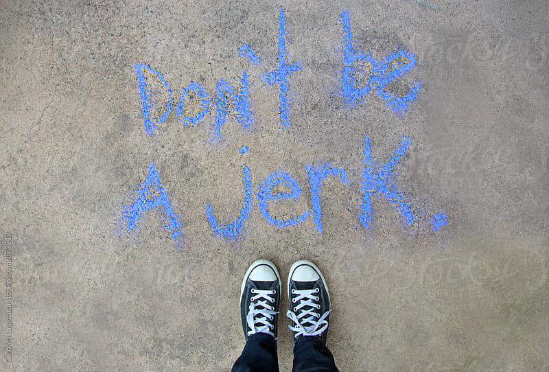 Person standing above chalk words that say Don't be a Jerk by Carolyn Lagattuta for Stocksy United
