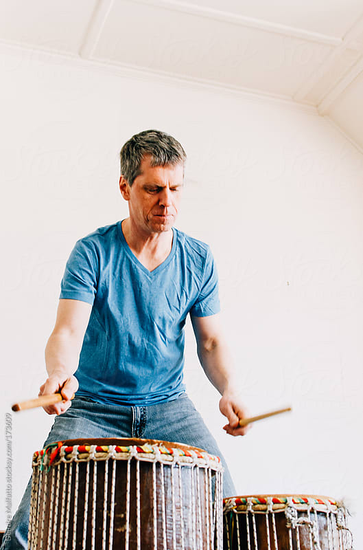man playing his hand drums by Deirdre Malfatto for Stocksy United