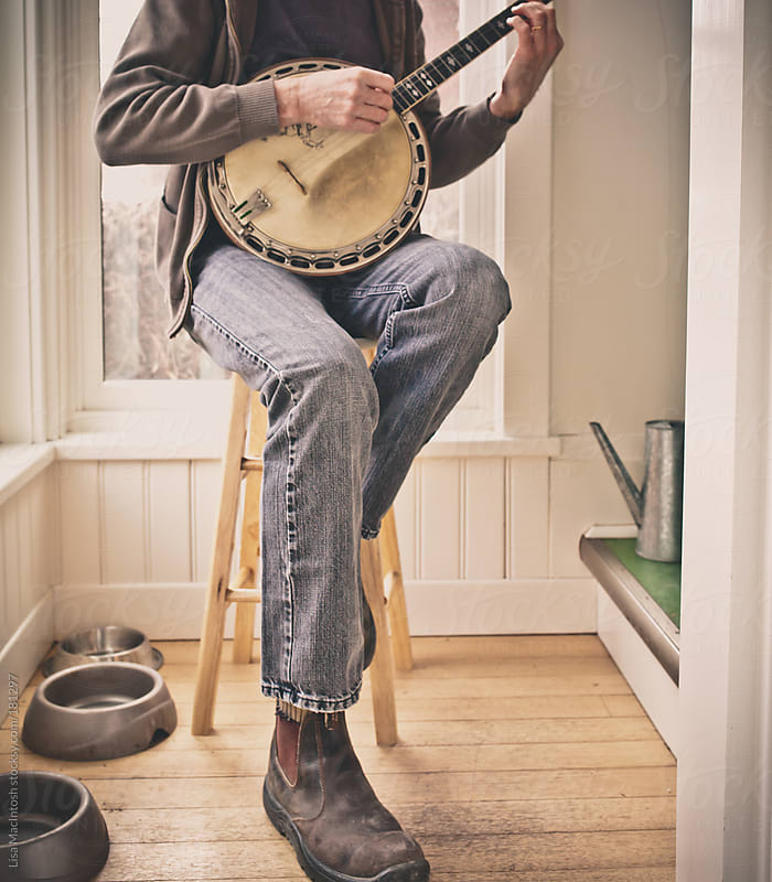man on yellow stool playing vintage banjo by Lisa MacIntosh for Stocksy United