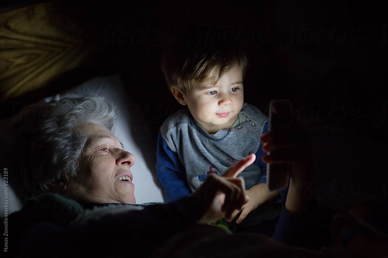 Grandmother with her grandson looking a smartphone in the dark by Nasos Zovoilis for Stocksy United