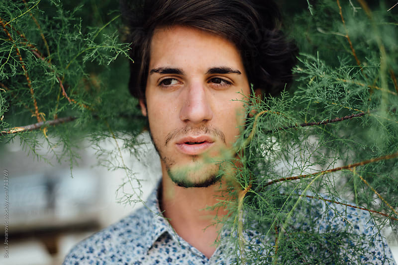 Portrait of man against the bush by Boris Jovanovic for Stocksy United