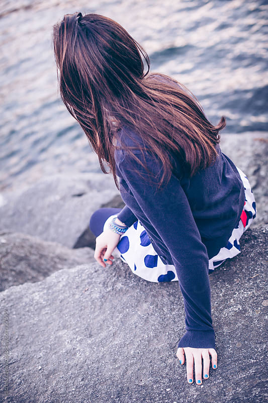Girl sitting on the rock. by michela ravasio for Stocksy United