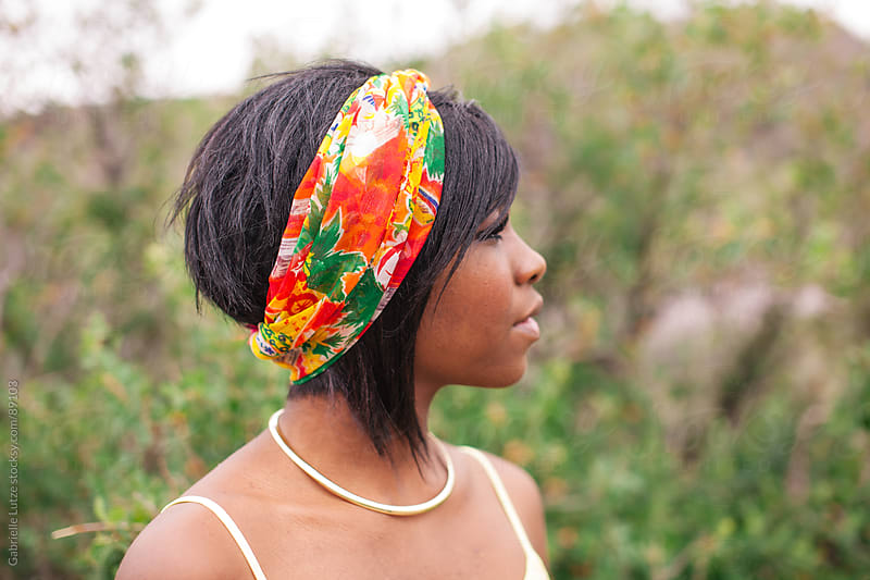 Close up of black girl wearing head scarf by Gabrielle Lutze for Stocksy United