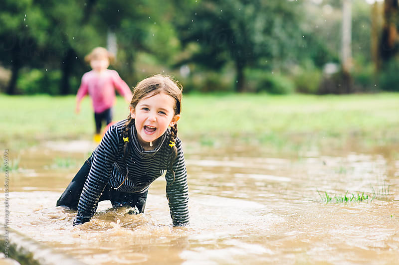 Little Girl Laughing after Falling in Puddle by Gary Radler Photography for Stocksy United