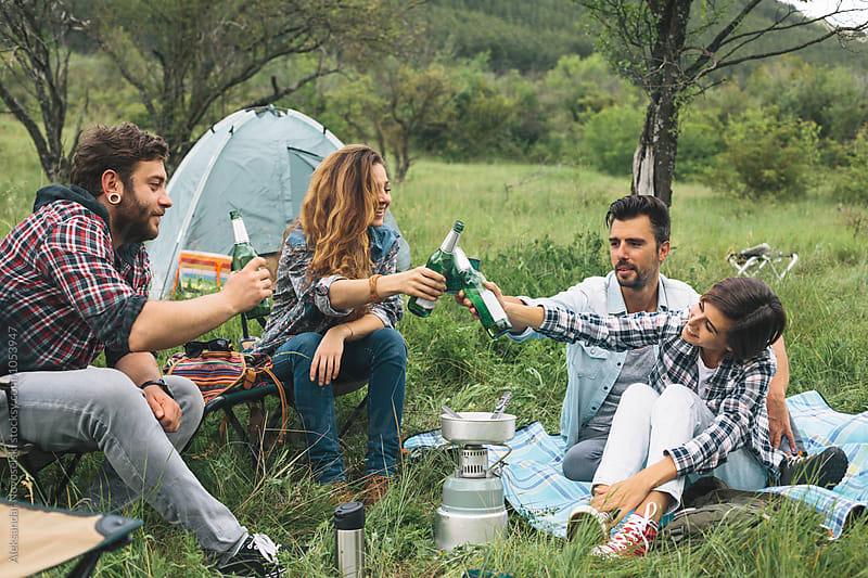 Friends camping and making a toast by Aleksandar Novoselski for Stocksy United
