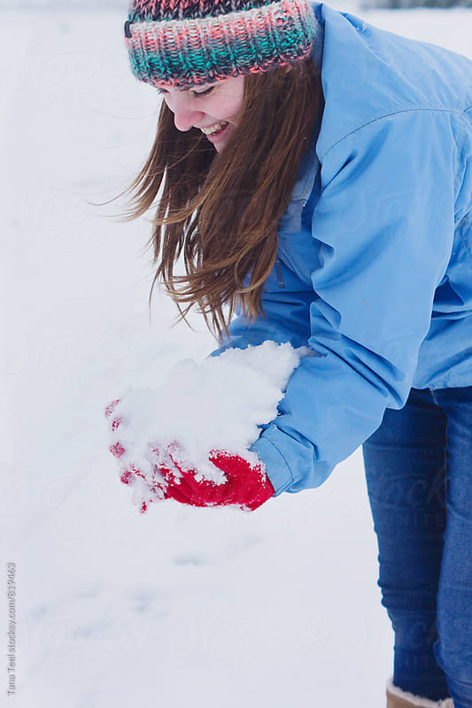 Teenager scoops up handfuls of snow by Tana Teel for Stocksy United