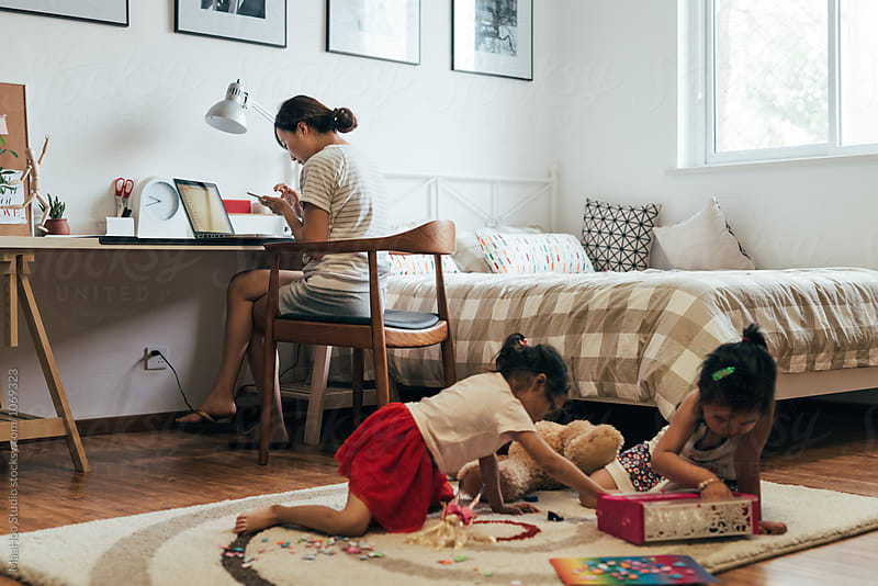 Mother working at laptop with children in background by MaaHoo Studio for Stocksy United