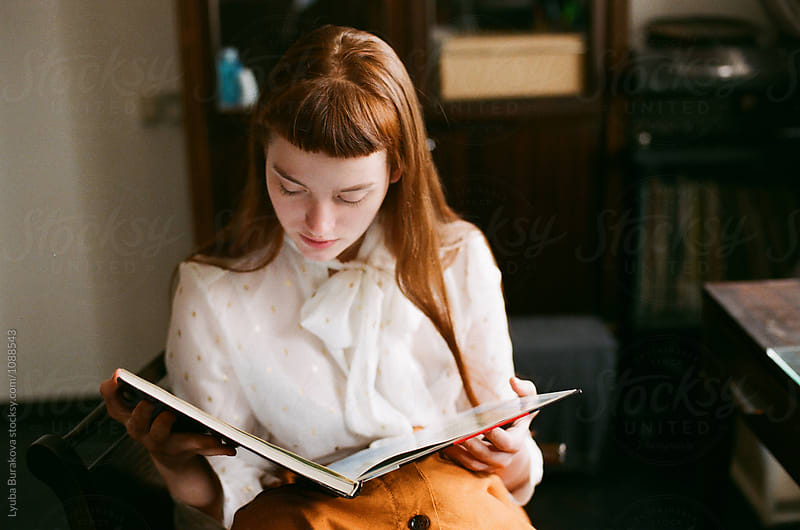 Young woman reading a book at home by Lyuba Burakova for Stocksy United