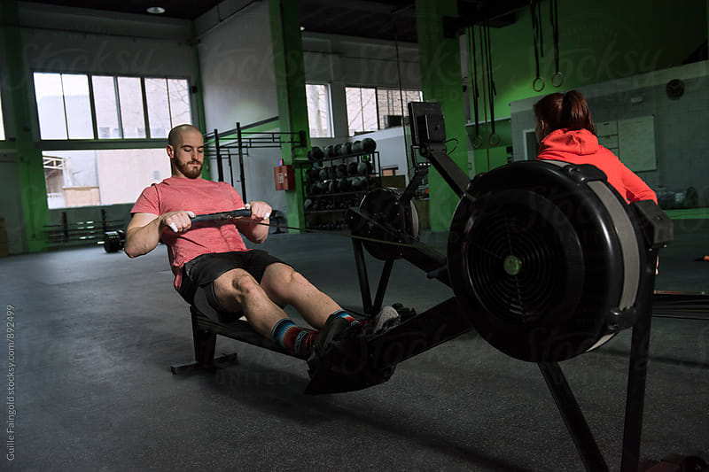Man and woman using rowing machine in gym by Guille Faingold for Stocksy United