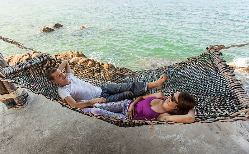 Couple Lying in the Hammock by the Sea by Mosuno for Stocksy United
